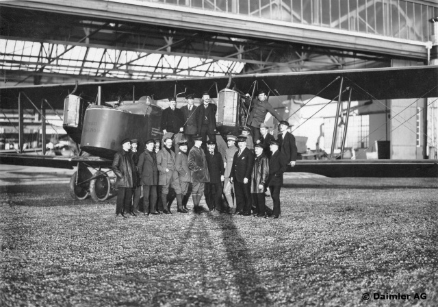 """Ein mit der """"Flugzeugbau-Friedrichshafen GmbH"""" (FF) am 28. September 1916 abgeschlossener Vertrag ermöglicht es der Daimler-Motoren-Gesellschaft, Flugzeuge der FF in Lizenz herzustellen und mit Daimler-Motoren auszurüsten. Hier das Großflugzeug G III mit zwei 260-PS/191 kW-Daimler-Mercedes-Flugmotoren, Typ D.IVa, 1916/1917, davor die stolzen Erbauer."""