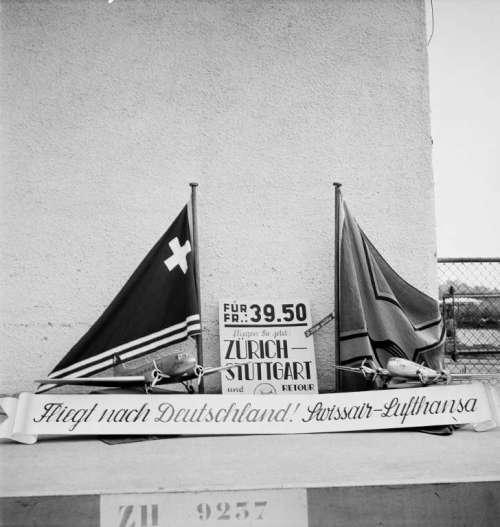 Links: Swissair-Fahne, rechts: Lufthansa-Fahne. Werbetext: Fliegen Sie jetzt Zürich-Stuttgart und retour für Fr. 39.50. Fliegt nach Deutschland! Swissair-Lufthansa